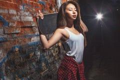 Ragazza teenager con il bordo del pattino, stile di vita urbano Fotografie Stock