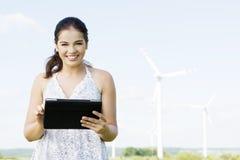 Ragazza teenager con il computer della compressa accanto al generatore eolico. Fotografia Stock