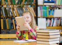 Ragazza teenager con il computer della compressa che funziona nella biblioteca Immagini Stock