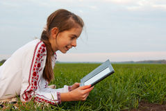Ragazza teenager con il libro elettronico che pone sull'erba Fotografia Stock