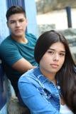 Ragazza teenager con il ragazzo teenager vago nella parte posteriore fotografie stock libere da diritti