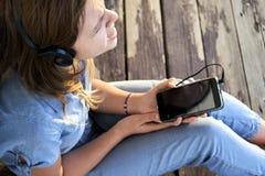 Ragazza teenager con le cuffie che ascolta e che gode della musica da uno smartphone immagine stock