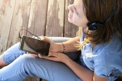 Ragazza teenager con le cuffie che ascolta e che gode della musica da uno smartphone fotografia stock