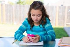 Ragazza teenager con lo smartphone che fa compito Immagini Stock