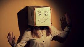 Ragazza teenager con una maschera divertente della scatola con il sorriso 60 a 24fps UHD archivi video