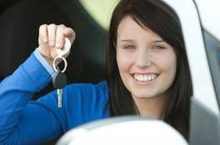 Ragazza teenager del Brunette che si siede nei suoi tasti della holding dell'automobile Immagini Stock