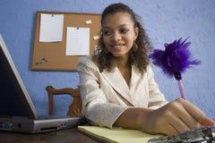 Ragazza teenager dell'afroamericano attraente allo scrittorio immagine stock libera da diritti