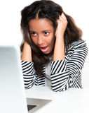 Ragazza teenager della corsa Mixed, scossa esaminando computer portatile Fotografie Stock
