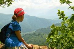 Ragazza teenager della viandante che si siede sull'alta scogliera in montagne armene nel giorno di estate soleggiato Immagini Stock