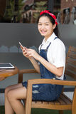 Ragazza teenager dello studente tailandese bella che usando il suoi Smart Phone e sorriso Fotografie Stock