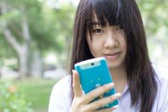 Ragazza teenager dello studente tailandese bella che utilizza il suo Smart Phone che si siede nel parco Immagini Stock Libere da Diritti