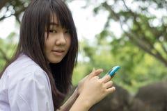 Ragazza teenager dello studente tailandese bella che utilizza il suo Smart Phone che si siede nel parco Fotografia Stock Libera da Diritti