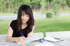 Ragazza teenager dello studente tailandese la bella scrive un libro che si siede in parco Fotografia Stock Libera da Diritti