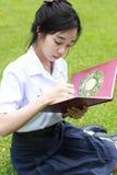 Ragazza teenager dello studente tailandese la bella scrive un libro che si siede in parco Fotografie Stock Libere da Diritti