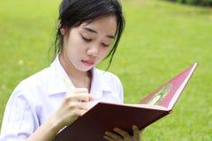 Ragazza teenager dello studente tailandese la bella scrive un libro che si siede in parco Immagine Stock