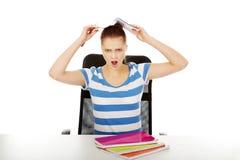 Ragazza teenager di grido con il libro sopra la sua testa Immagini Stock