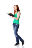 Ragazza teenager diritta che legge un libro. Fotografia Stock