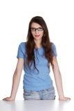 Ragazza teenager felice che si leva in piedi dietro lo scrittorio Fotografia Stock Libera da Diritti