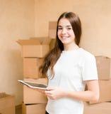 Ragazza teenager felice con il computer della compressa che sta su un fondo delle scatole Immagini Stock