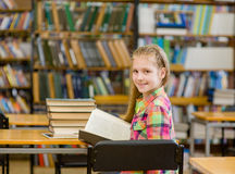 Ragazza teenager felice con lo sguardo del libro indietro in biblioteca Fotografia Stock