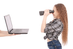 Ragazza teenager felice della scuola che per mezzo del binocolo che esamina lo schermo del computer portatile Fotografia Stock