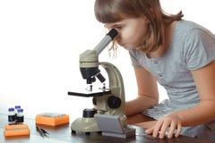 Ragazza teenager nel laboratorio della scuola Ricercatore che lavora con il microscopio Fotografia Stock