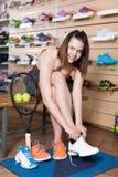 Ragazza teenager positiva che prova le scarpe da tennis professionali Immagine Stock