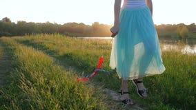 Ragazza teenager positiva di risata con i nastri in mani che cammina sulla natura verde vicino al lago video d archivio