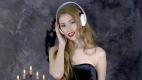Ragazza teenager sorridente attraente con le cuffie, colpo in uno studio Donna castana attraente che registra una canzone nella m stock footage