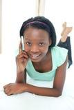 Ragazza teenager sorridente che per mezzo di un telefono mobile Immagine Stock Libera da Diritti