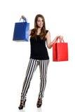 Ragazza teenager sorridente con i sacchetti della spesa variopinti Immagine Stock