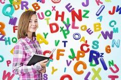 Ragazza teenager sorridente in una camicia rosa, libro, lettere Immagine Stock