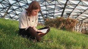 Ragazza teenager in una camicia grigia che si siede sull'erba nel parco e che legge un taccuino con le note di conferenza un gior video d archivio