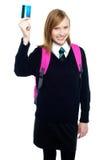 Ragazza teenager in uniforme che sostiene una scheda di contanti Fotografie Stock Libere da Diritti