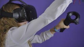 Ragazza teenager in vetri virtuali su un fondo di fondo porpora stock footage