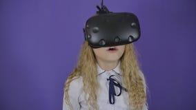 Ragazza teenager in vetri virtuali su un fondo porpora archivi video