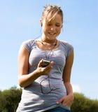 Ragazza, telefono mobile e trasduttori auricolari Fotografia Stock Libera da Diritti