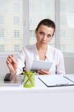 Ragazza tenendo una compressa che si siede alla tavola Fotografia Stock