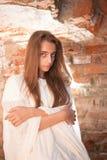 Ragazza in tessuto bianco vicino al muro di mattoni Fotografie Stock