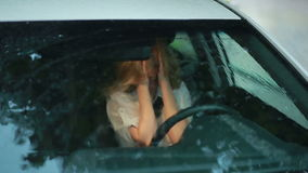 Ragazza triste che grida nell'automobile Pioggia sulla via donna nell'attacco isterico