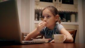 Ragazza triste che mangia spuntino e che considera lo schermo di computer portatile alla tavola in cucina archivi video