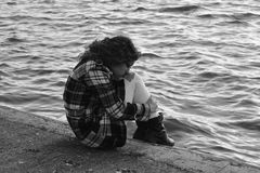Ragazza triste che si siede dal lago depressione Fotografie Stock Libere da Diritti