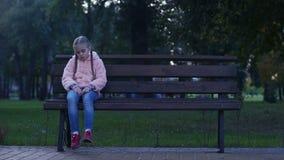 Ragazza triste che si siede sul banco in parco, bambino mancante perso, genitori aspettanti della scuola archivi video