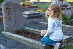 Ragazza triste davanti alla tomba fotografia stock