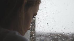 Ragazza triste dell'adolescente che guarda esterno attraverso la finestra nel giorno piovoso video d archivio