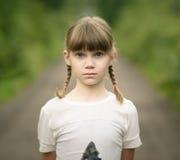 ragazza triste dell'adolescente con due trecce che stanno sulla strada rurale Fotografie Stock Libere da Diritti