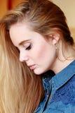 Ragazza triste nel profilo, capelli di diffusione, in una camicia del denim Immagine Stock