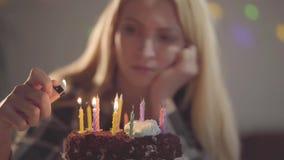 Ragazza triste sola che si siede davanti a poche candele di illuminazione del dolce La donna infelice ha festa di compleanno Conc video d archivio
