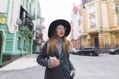 Ragazza turistica alla moda che passeggia tramite le vie di vecchia città con le cuffie ed i sorrisi Immagini Stock