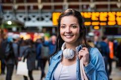 Ragazza turistica in camicia del denim con le cuffie Stazione ferroviaria Fotografie Stock